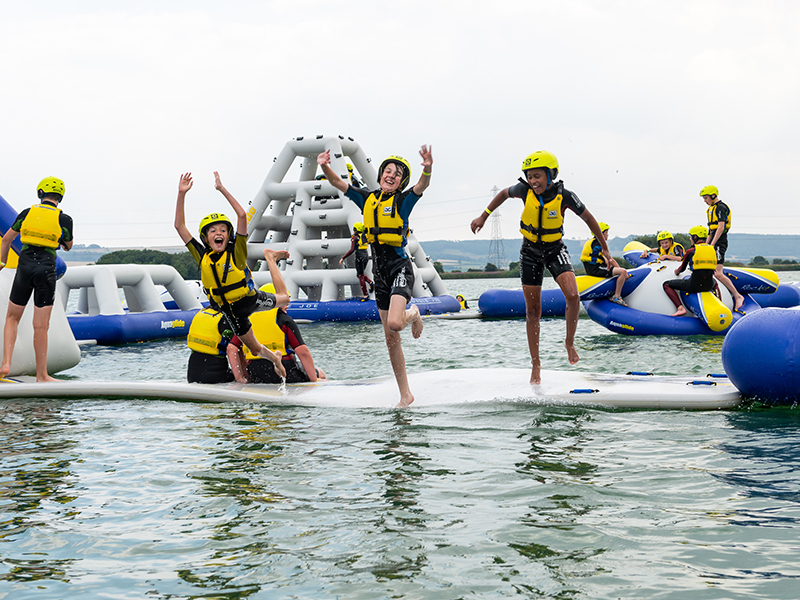 Group jumping off inflatable assault course into water