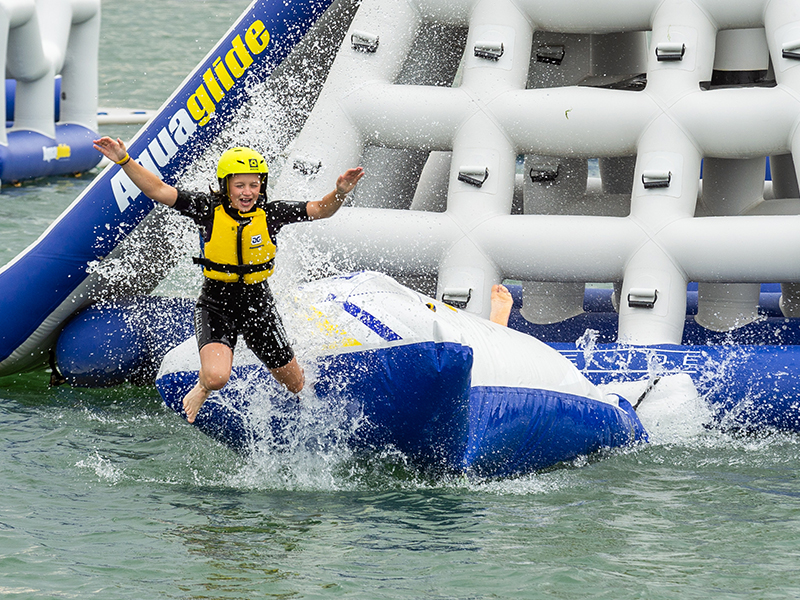 Boy jumping off inflatable assault course into water
