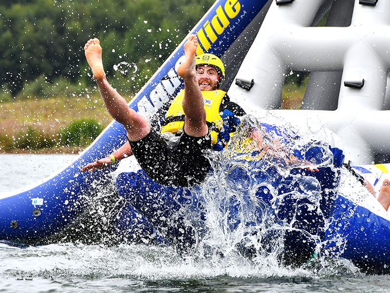 Man jumping off inflatable water assault course