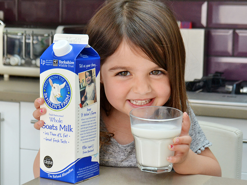 Girl holding carton and glass of milk