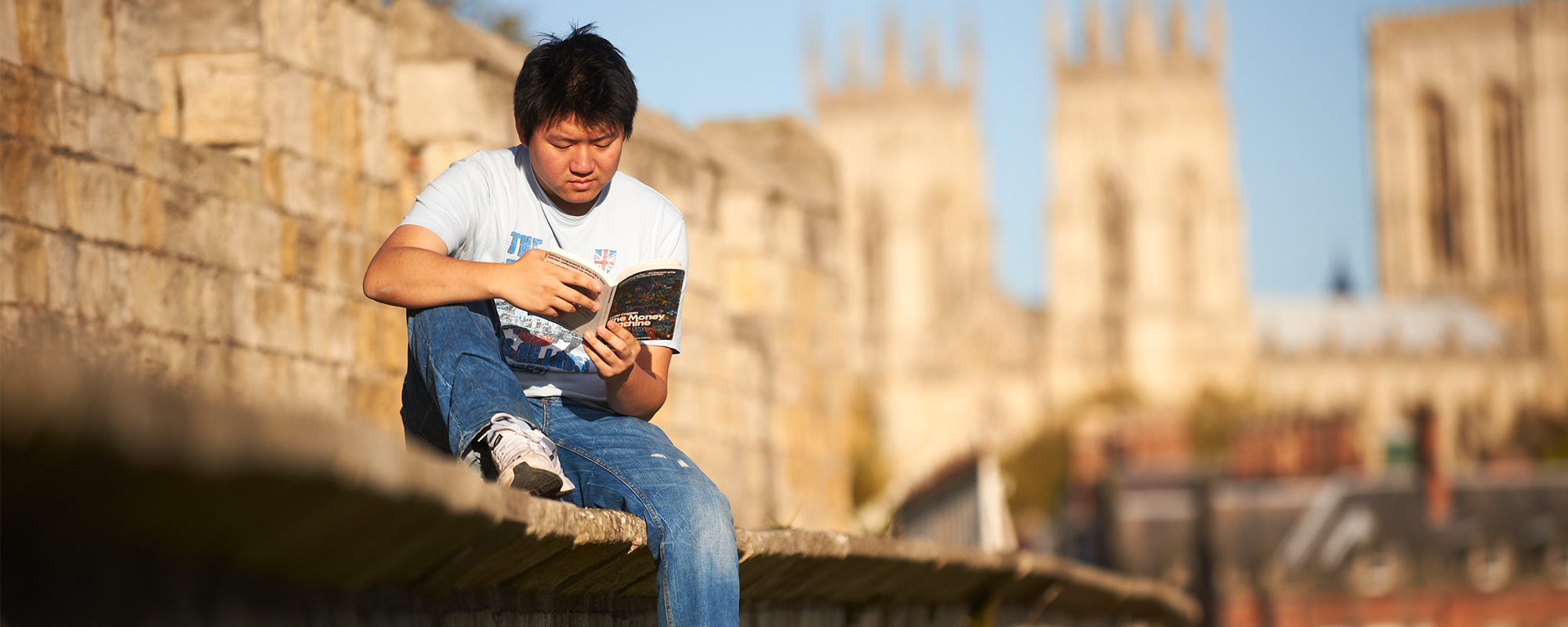 Student sat on York walls reading a book