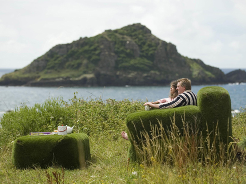 Couple sat outside on turfed sofa