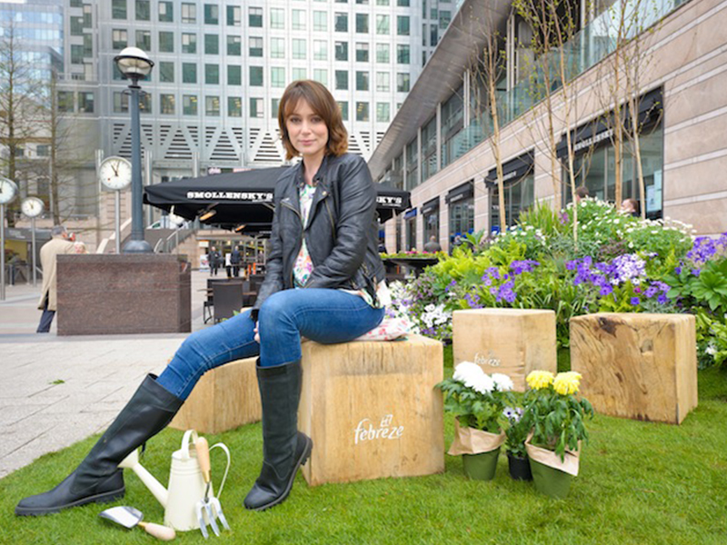 Woman sat on wooden box on lawn