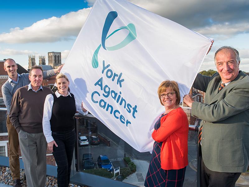 York Against Cancer team holding up York Against Cancer flag